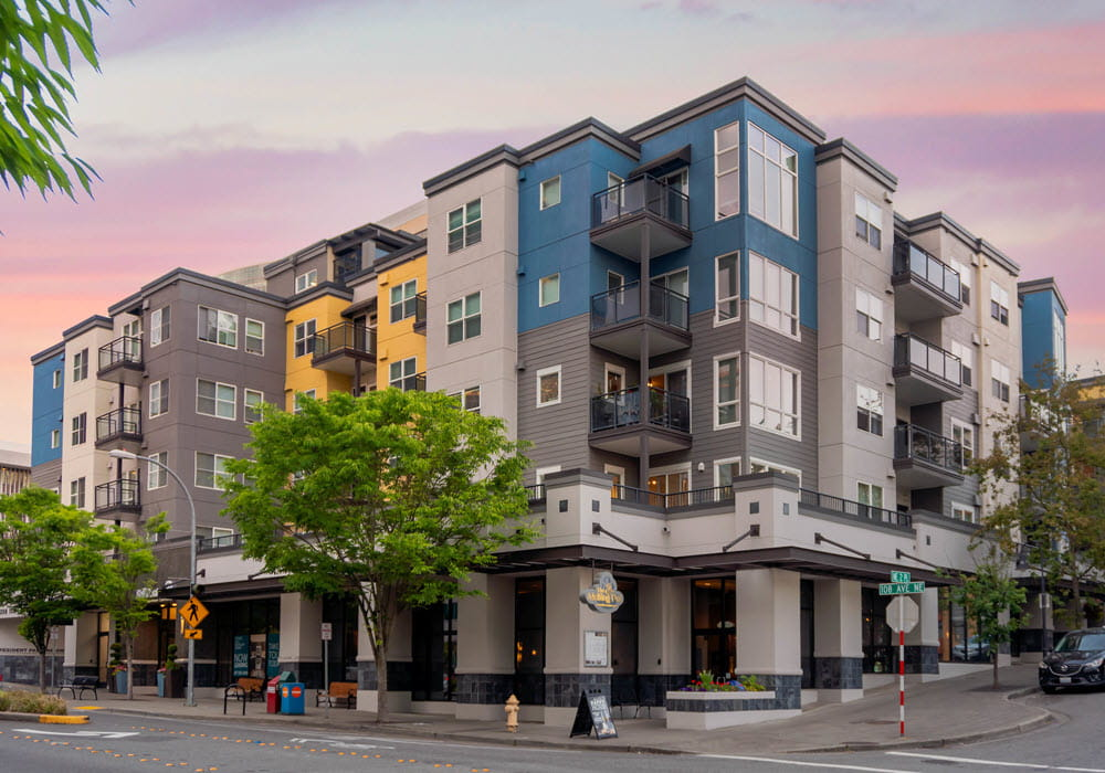 Exterior view of BellCentre Apartments in Seattle at dusk.