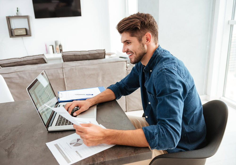 Man checking his credit score via his laptop from his apartment home.