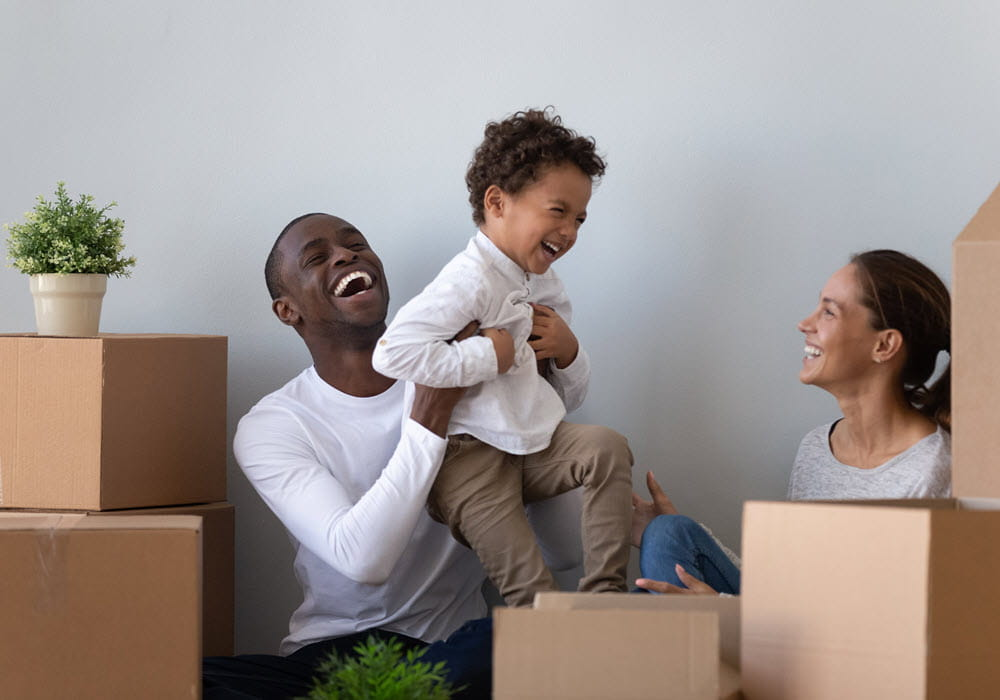 Family of 3 unboxing their moving boxes in their apartment home.