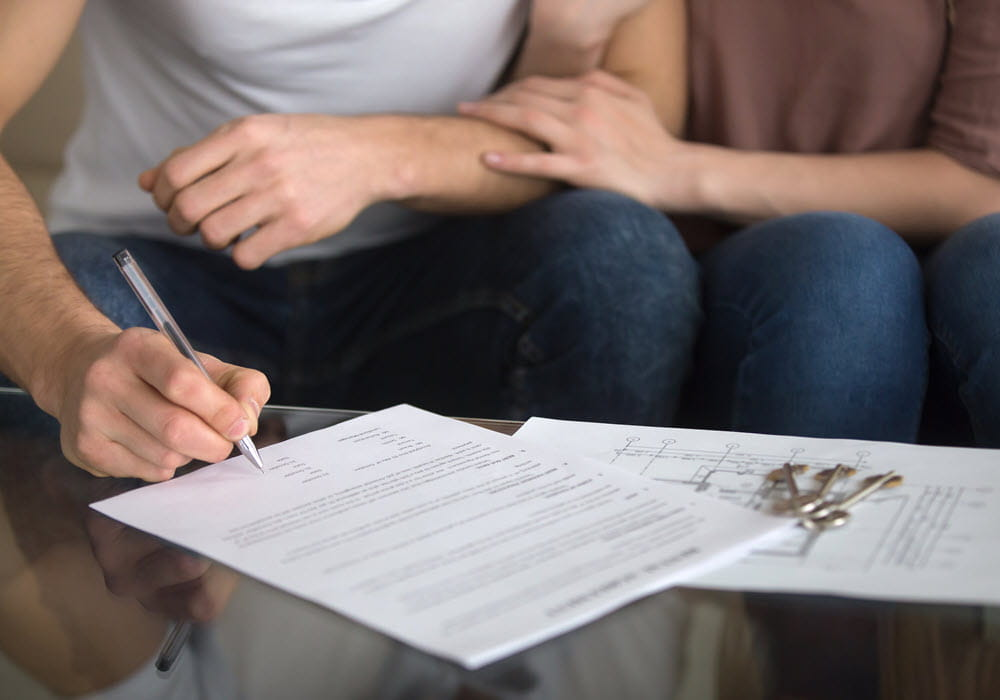 Couple doing paperwork to renew an apartment lease.