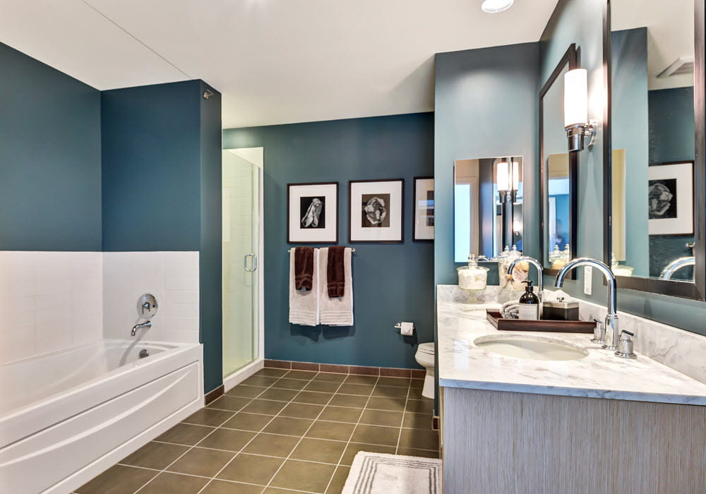 Staged apartment bathroom with teal accent walls.