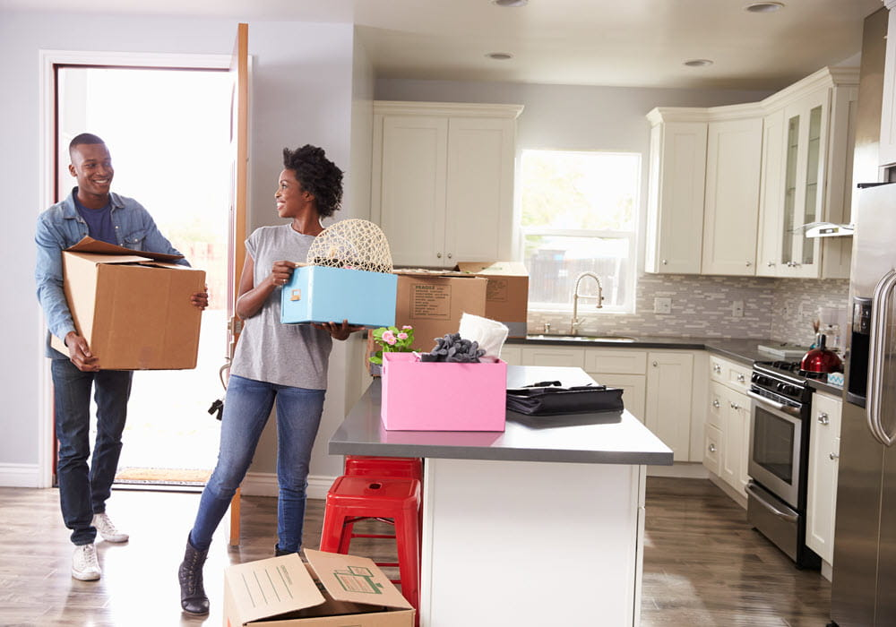 Couple carrying moving boxes into an apartment.