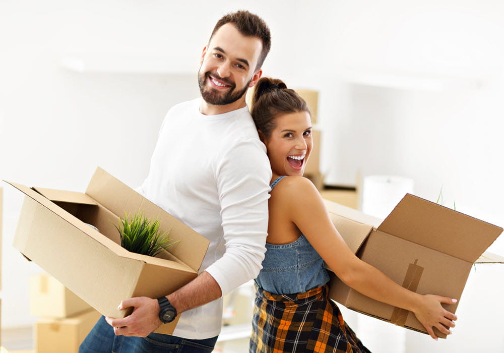 Couple holding moving boxes.