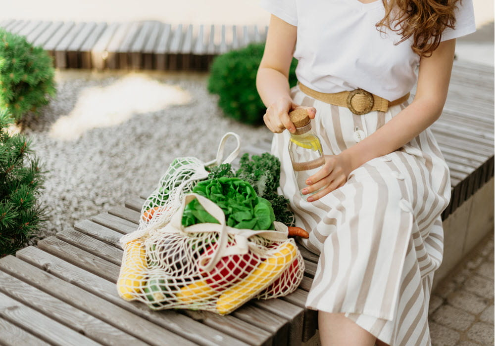 Woman sitting next to a eco-friendly bag full of produce.