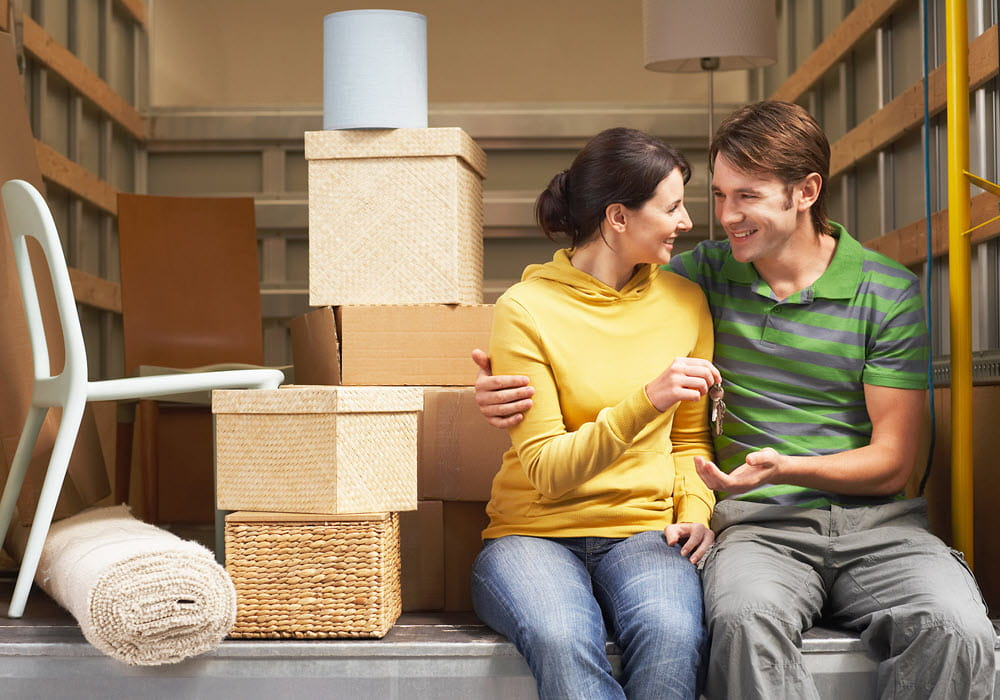 Couple sitting in moving truck next to their moving boxes.