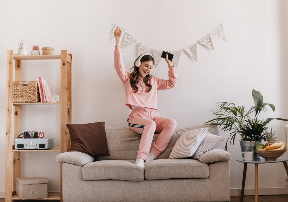 woman dancing on couch in apartment living room